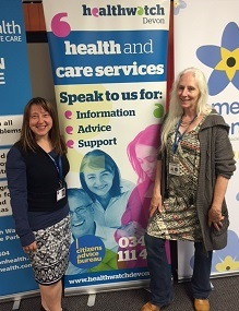 two Healthwatch champions with a Healthwatch display stand